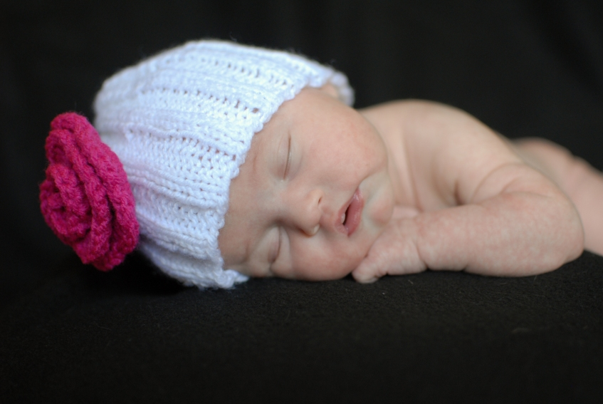 newborn girl with white hat and pink flower