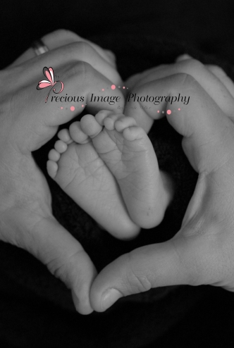 newborn baby feet with dads hand in a heart