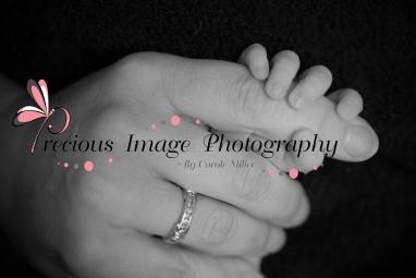 moms hand with newborns hand wrapped around