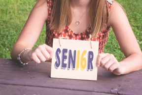 girl holding senior sign in school colors