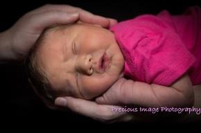 newborn girl in loving hands