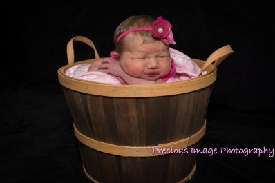 newborn girl wearing headband in basket