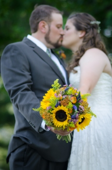 bride and groom kissing holding the bouquet at the Country Barn in Lancaster, PA