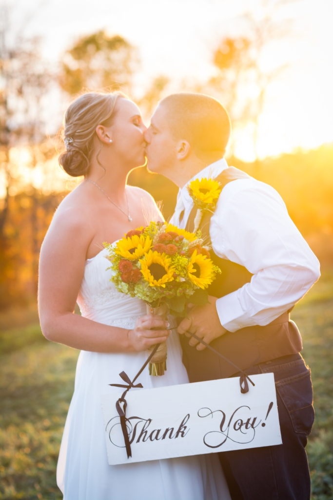 wedding couple kissing in the sunset holding a thank you sign