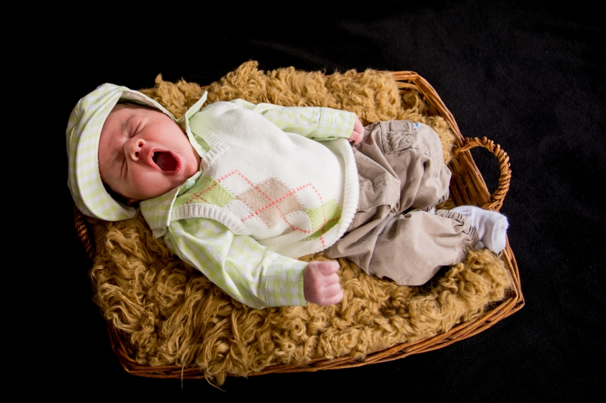 newborn boy in a basket yawning