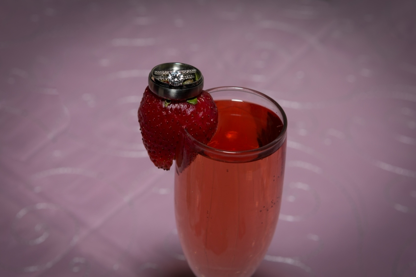 wedding rings on strawberry champagne glass