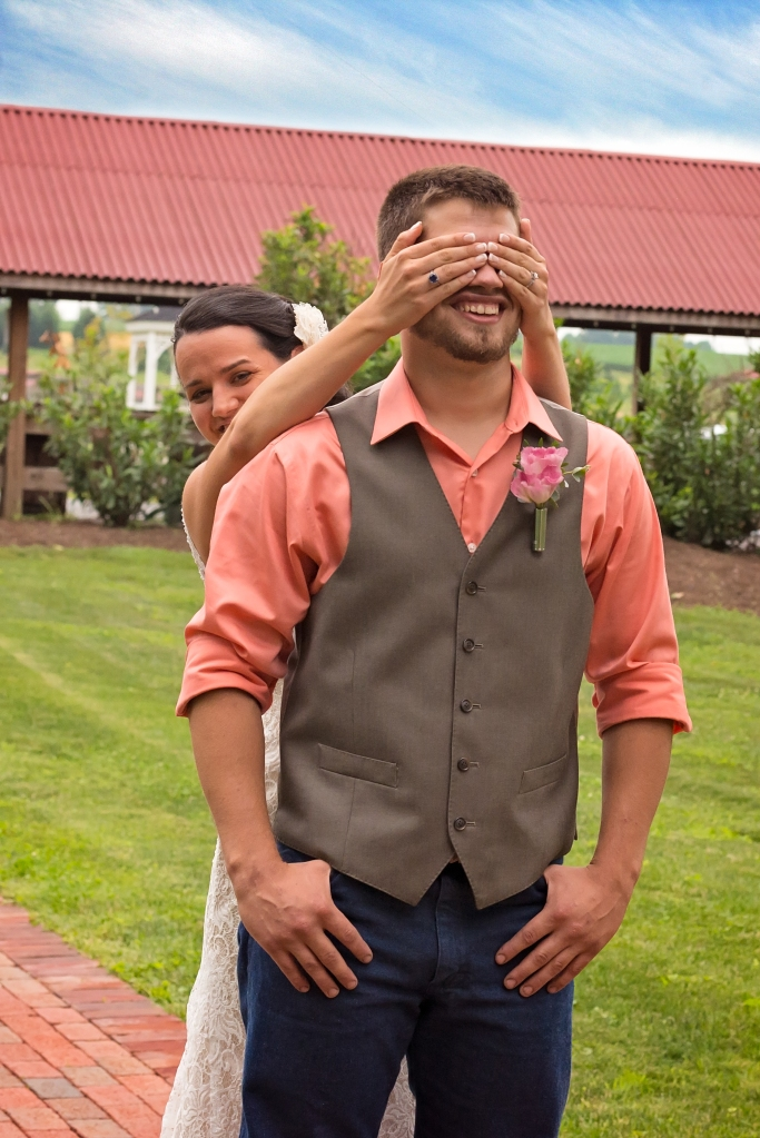 Bride covering grooms eyes before he sees her