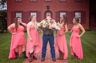 Groom laughing at the bridesmaids because he stole their flowers