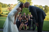 wedding photo with couple kissing and wedding party behind them