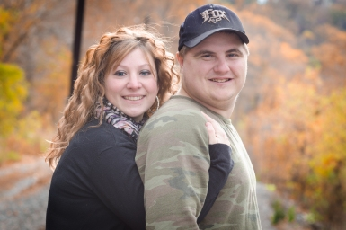 engagement couple with trees and leaves in fall surrounding them