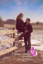 engagement couple sitting on the fence with a beautiful blue sky background