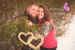 engagement couple posing by tree with hearts