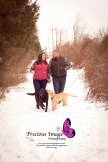 couple holding hands and walking dogs in the snowy woods engagement session