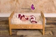 baby boy in bed on wood floor backdrop