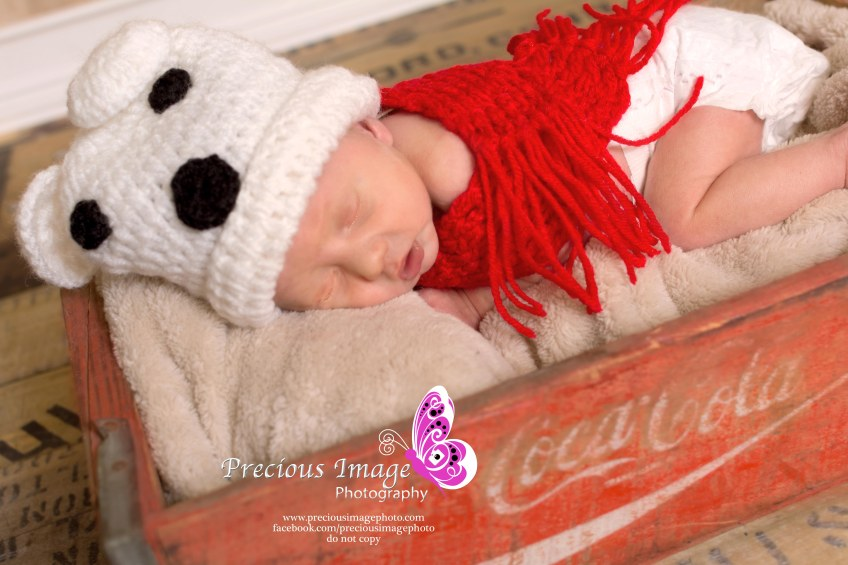 newborn wearing polar bear outfit in coke cola box
