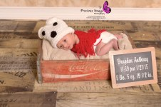 newborn with chalkboard wearing polar bear outfit in coke cola box