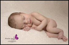 baby girl posed on white fluffy background