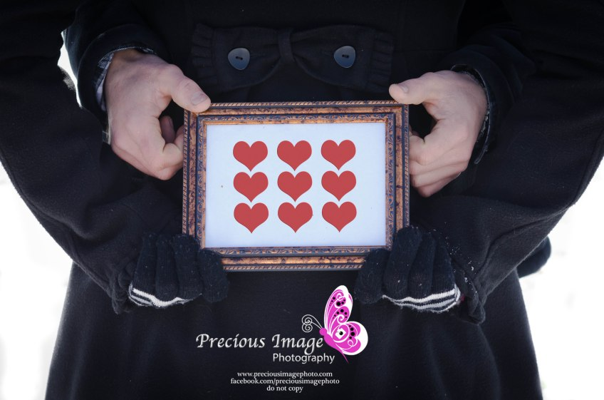 photo of frame with hearts being held by couples hands
