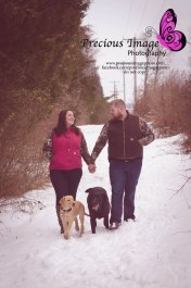 engagement couple with dogs in the snowy woods
