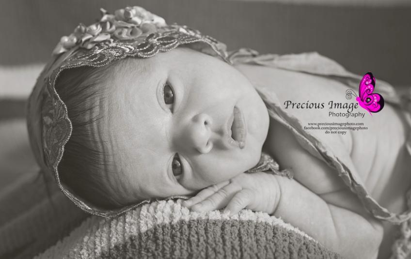 newborn girl wearing bonnet